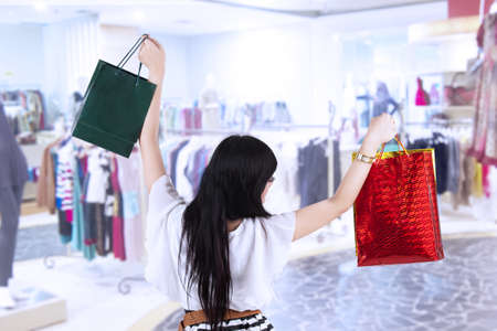 Excited woman with shopping bags in the mall photo