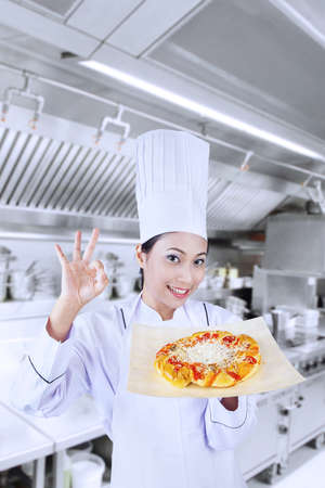 chefs whites: Asian female chef is holding a pizza with OK sign in the kitchen Stock Photo