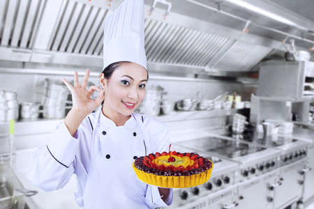 whites: Beautiful Asian chef is showing OK sign while holding fruit cake