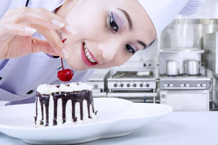 chefs whites: Beautiful young female chef is decorating chocolate cake Stock Photo