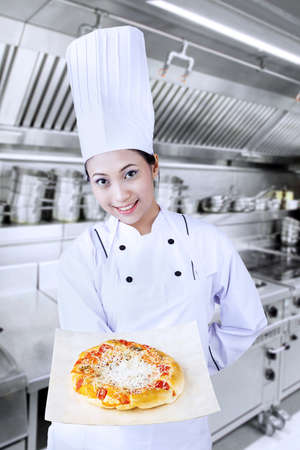 Young female chef is serving pizza photo