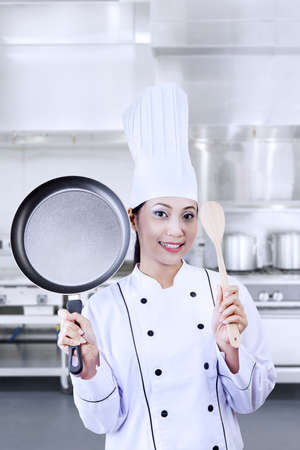 Female chef holding a pan and wooden spoon photo