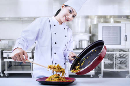 whites: Asian chef is pouring fried noodle in the kitchen Stock Photo