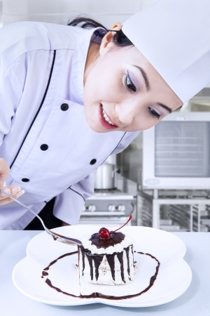 Beautiful chef is preparing a chocolate dessert in the kitchen photo