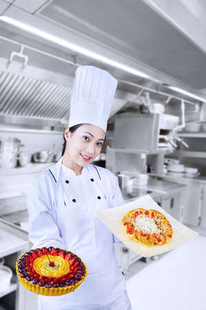 whites: Beautiful chef is serving fruit cake and pizza