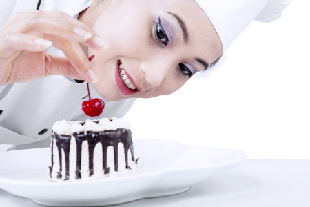 chefs whites: Beautiful chef decorating chocolate cake on white background