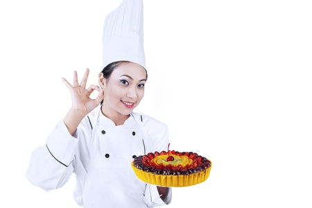 Beautiful chef giving OK sign while holding delicious fruit cake photo