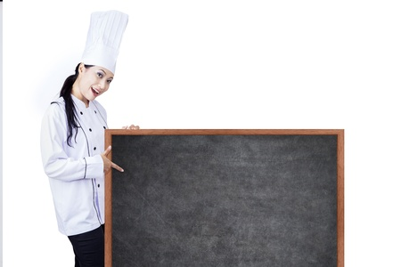 Beautiful Asian chef is holding a blank blackboard to show todays menu photo