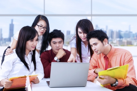 indonesian: Business team is having a meeting in office using laptop Stock Photo