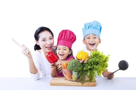 Moeder en chef kinderen zijn klaar om groente koken op een witte achtergrond