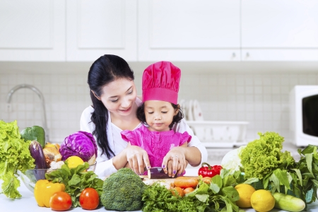 kitchen aprons: Chef girl is learning how to cut vegetables with mom in the kitchen