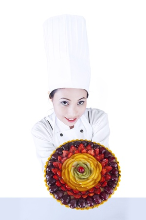 Beautiful chef showing the fruit cake on white background photo