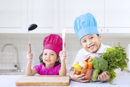 blue white kitchen: Cute little Asian chef with vegetables