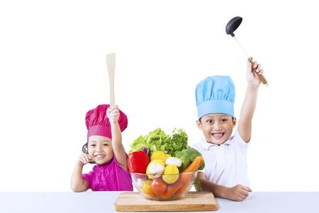 ni�os cocinando: Ni�os asi�ticos con cocinero sombrero y vetegable