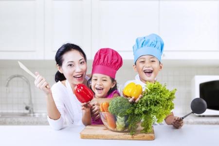Gelukkig gezin kookt in de keuken bij elkaar
