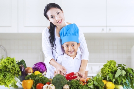 Mom and her little boy cook vegetable together at home photo