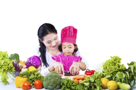 japanese cooking: Mom is showing her daughter how to cut vegetables on white background
