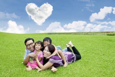asia family: Familia asi�tica se divierte en el parque bajo las nubes de forma de coraz�n Foto de archivo