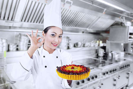 Beautiful Asian chef is showing OK sign while holding fruit cake Stock Photo - 18544595