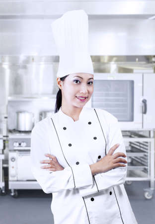 Beautiful chef with crossed arms on kitchen photo