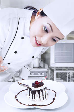 food and drink industry: Beautiful chef is preparing a chocolate dessert in the kitchen