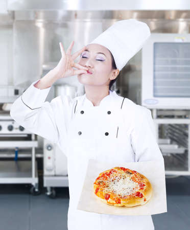 chefs whites: Asian chef holding pizza and giving OK sign on kitchen