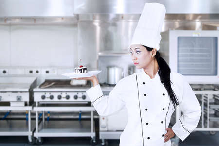 Asian chef serving a chocolate cake with elegant style photo