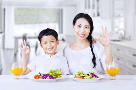 Asian family are making OK gesture while having salad at home photo