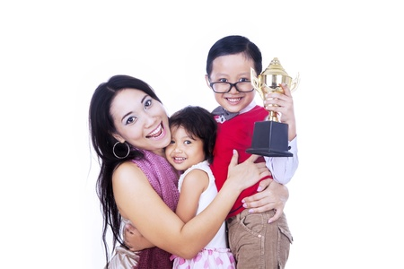 Little boy is celebrating his winning with his mother and little sister, isolated on white photo