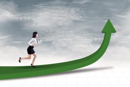 upward graph: Businesswoman running on arrow sign under blue sky Stock Photo