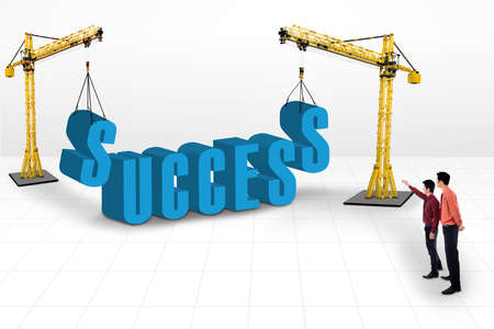 Building success concept using two cranes with businessmen pointing at it Stock Photo - 18632452