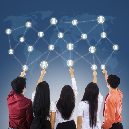 Five business people pointing at touchscreen to make connections Stock Photo - 18632465