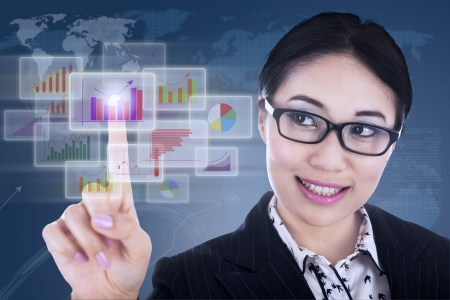 Businesswoman is clicking on futuristic touchscreen with diagrams photo