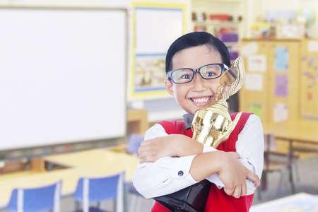primer lugar: Boy es la celebración de un trofeo y orgulloso de su logro, aislado en blanco