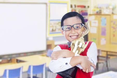 first place: Boy is holding a trophy and proud of his achievement, isolated on white Stock Photo