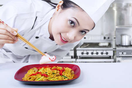 chinese hat: Beautiful Asian chef prepares fried noodle in kitchen