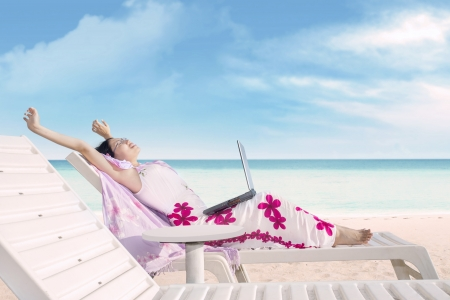 getting away from it all: Attractive Asian woman is relaxing at the beach while working with her laptop