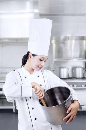 stirring: Beautiful chef is stirring chocolate in kitchen