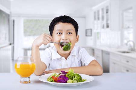 man eten: Gelukkige jongen is het eten van salade met broccoli erin thuis