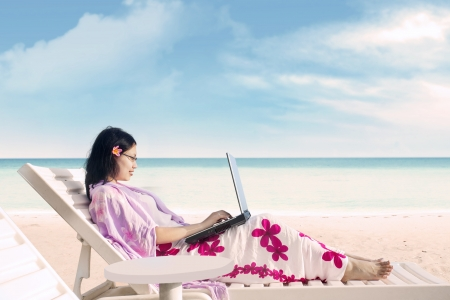 away from it all: Asian woman is working with her laptop at the beach