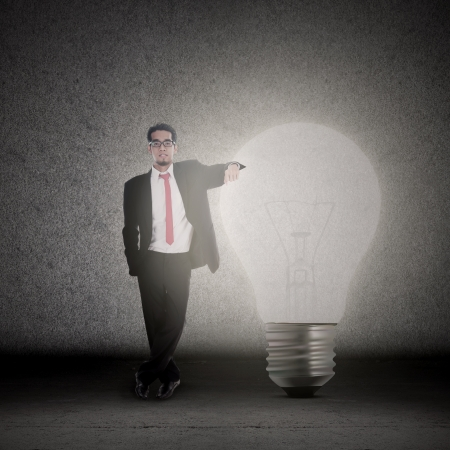 Businessman has bright idea, standing beside a bright light bulb Stock Photo - 18692830