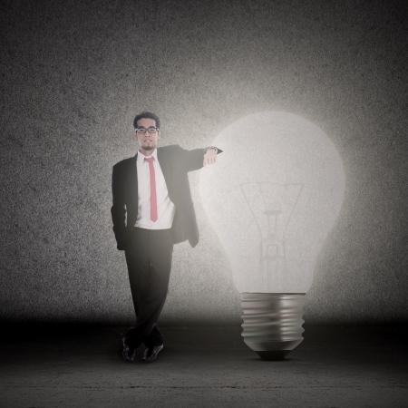 Businessman has bright idea, standing beside a bright light bulb Stock Photo - 18692830