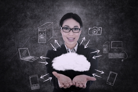 Businesswoman offering cloud computing on chalkboard background photo