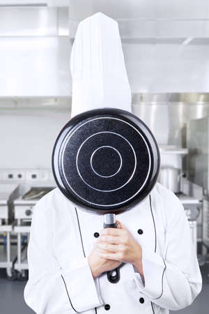 Chef is hiding behind a saucepan in the kitchen photo