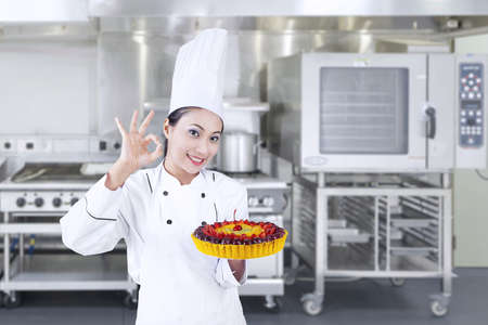 Beautiful chef is holding fruit cake at the kitchen , horizontal shot photo