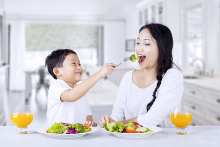 Mother and son are eating green salad at home Stock Photo - 18692809