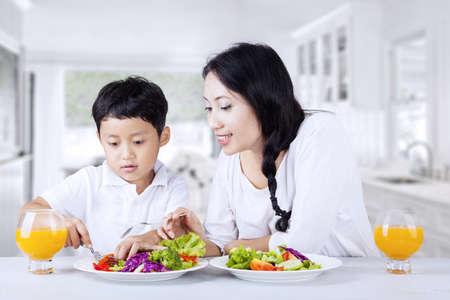 familia comiendo: La madre está animando a su hijo a comer ensalada en casa