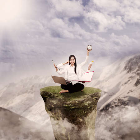 Young entrepreneur is multitasking on top of a mountain rock photo