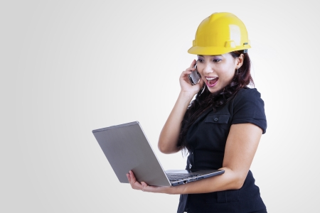 Happy architect is laughing on the phone while holding her laptop, isolated on white photo