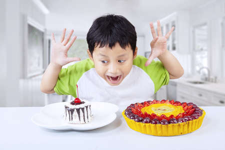 Excited boy choosing between two desserts at home photo